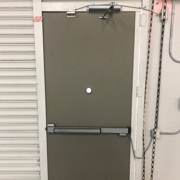 Commercial back of house door with closer, push bar, and additional security features installed in an industrial property