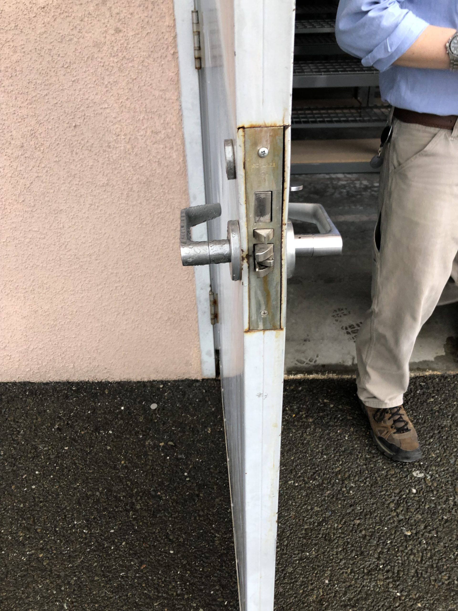 commercial lock being replaced on exterior door behind the building